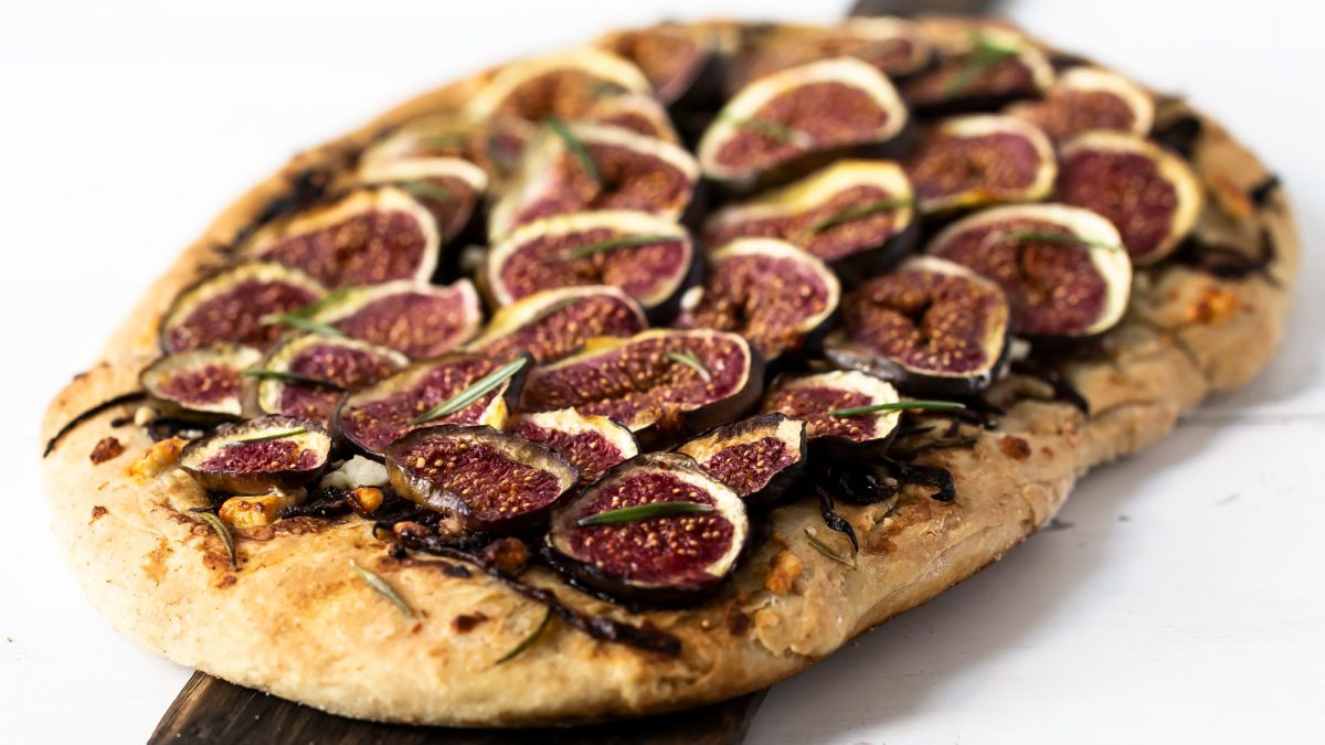Feigenpizza angerichtet auf Holzbrett