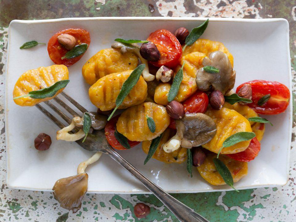 Kürbis-Gnocchi angerichtet mit Pilzen, Tomaten und Nüssen
