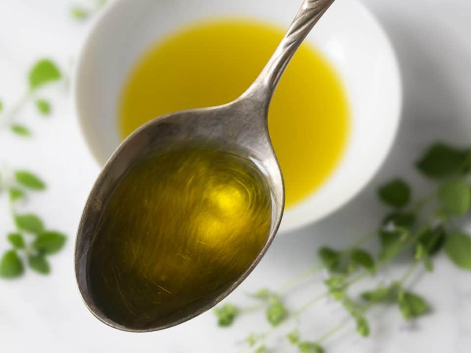 Oliveöl auf Löffel vor unscharfem Hintergrund