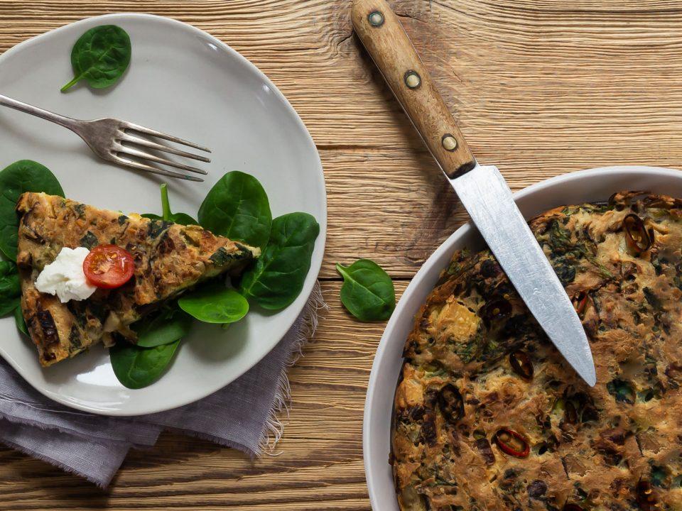 Vegane Gemüse-Quiche angerichtet mit Babyspinat und Joghurt