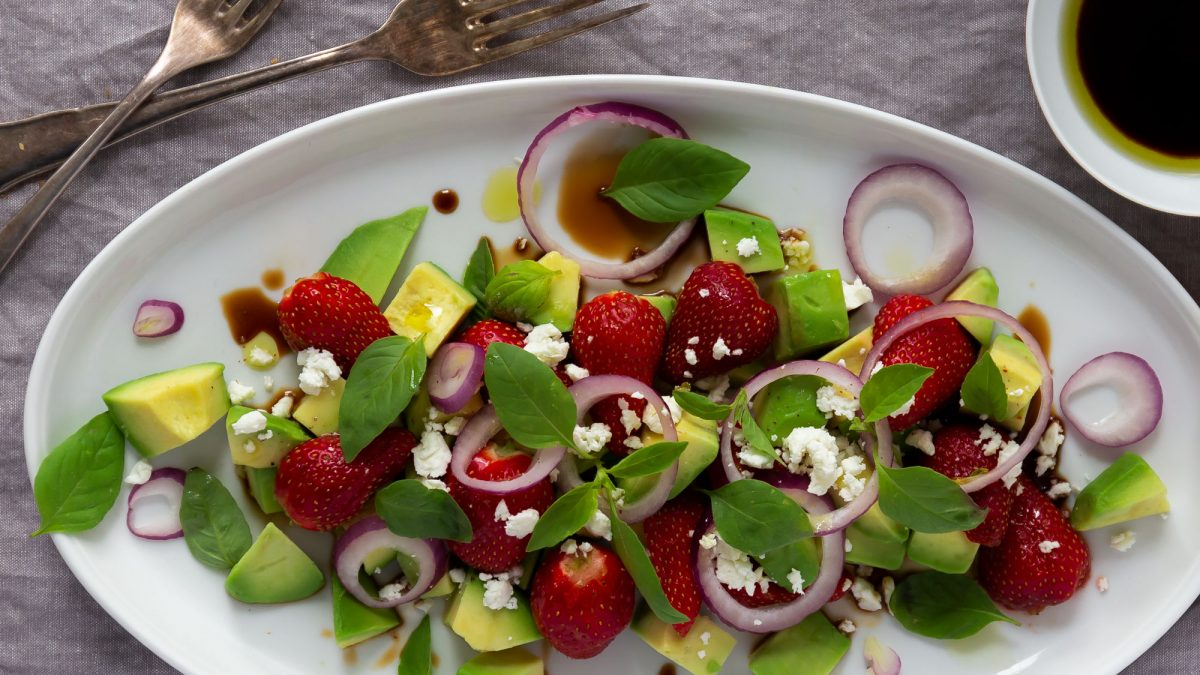 Avocado-Erdbeer-Salat mit Feta angerichtet auf einer Platte mit einer Reduktion aus NOAN Apfelbalsam