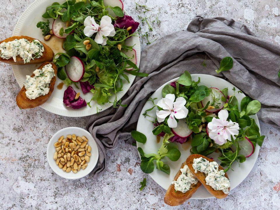 Frühlings-Salat mit Blüten angerichtet mit geröstetem Brot mit Frischkäse