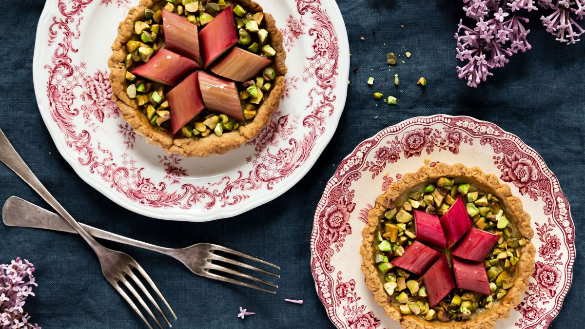 Rhabarber-Tartelettes auf vintage-Tellern mit gehackten Pistazien angerichtet