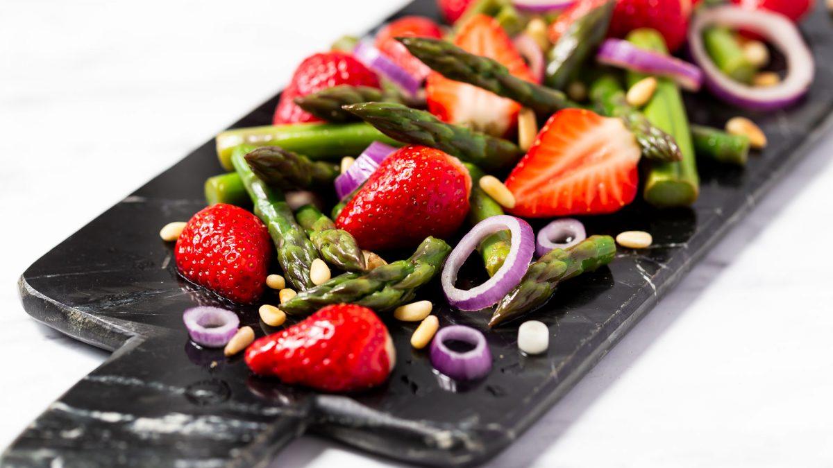 Spargel-Salat mit Erdbeeren angerichtet auf einem Marmor-Brett