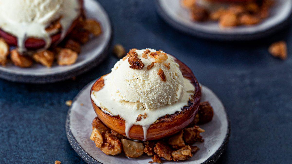 Gegrillte Pfirsiche mit Eis und Krokant angerichtet auf handgefertigten Tellern