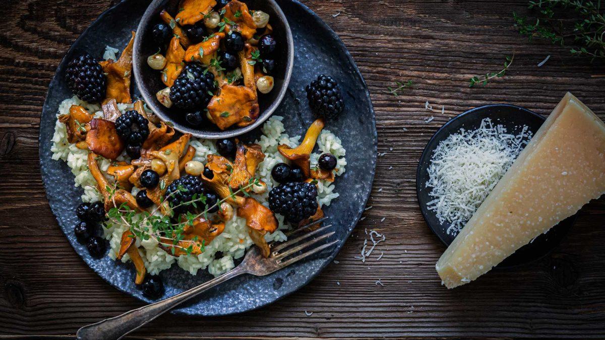 Eierschwammerl-Risotto angerichtet mit Brombeeren auf einem Steinteller mit geriebenem Parmesan