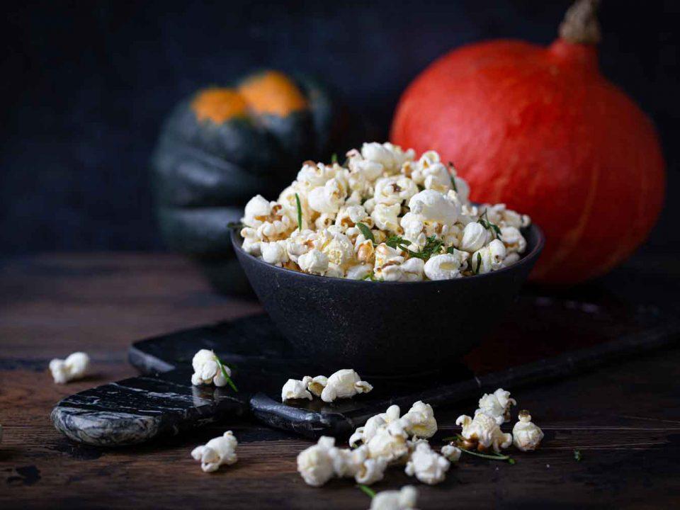 Kräuter-Popcorn, angerichtet in einer dunnklen Schussel in einem herbstlichen Setting