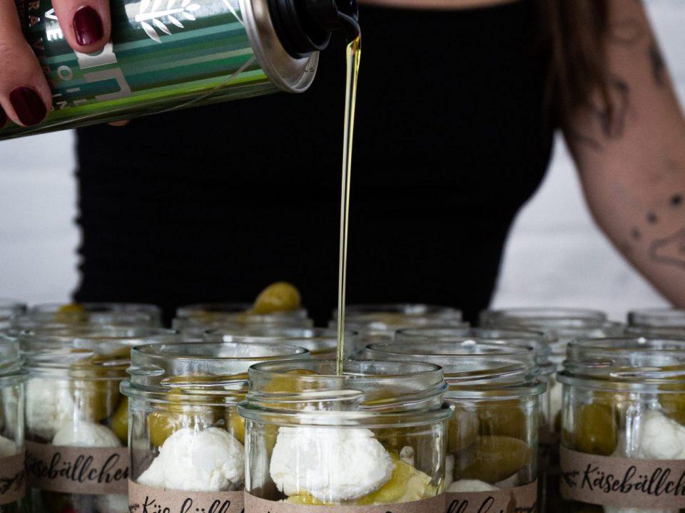 Eine Frau gießt NOAN Herbs Kräuter-Olivenöl in Gläser mit Ziegenkäsebällchen