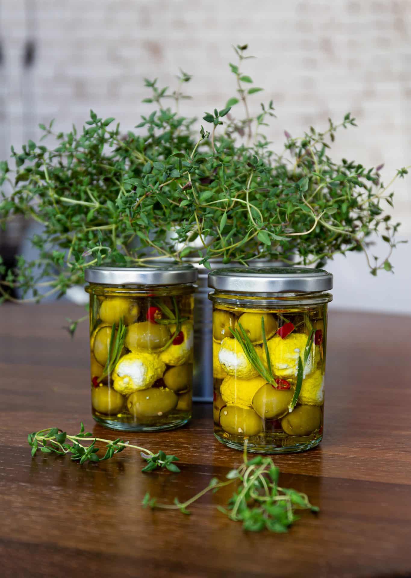 Fertige Gläser mit Ziegenkäsebällchen und Kräuter-Olivenöl