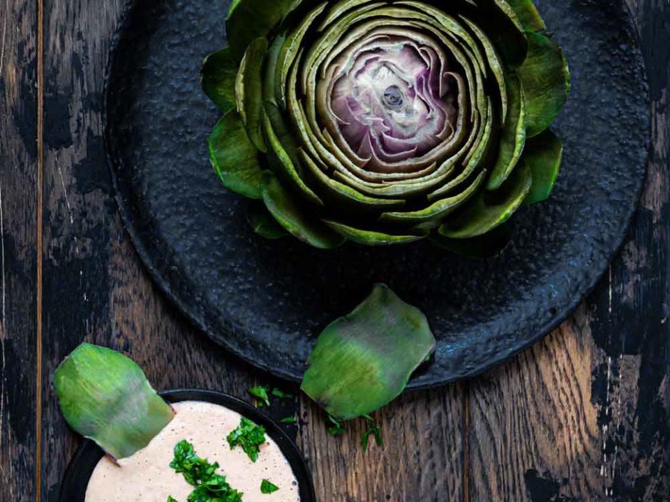 Artischocke auf dunklem Teller angerichtet mit Vinaigrette in Variante zwei