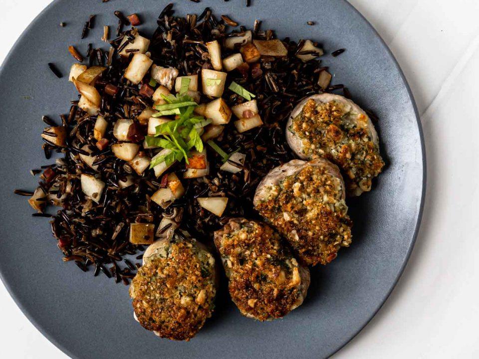 Schweinemedaillons mit Macadamia-Kruste angerichtet mit wildem Birnen-Reis auf einem dunklen Teller mit herbstlicher Deko