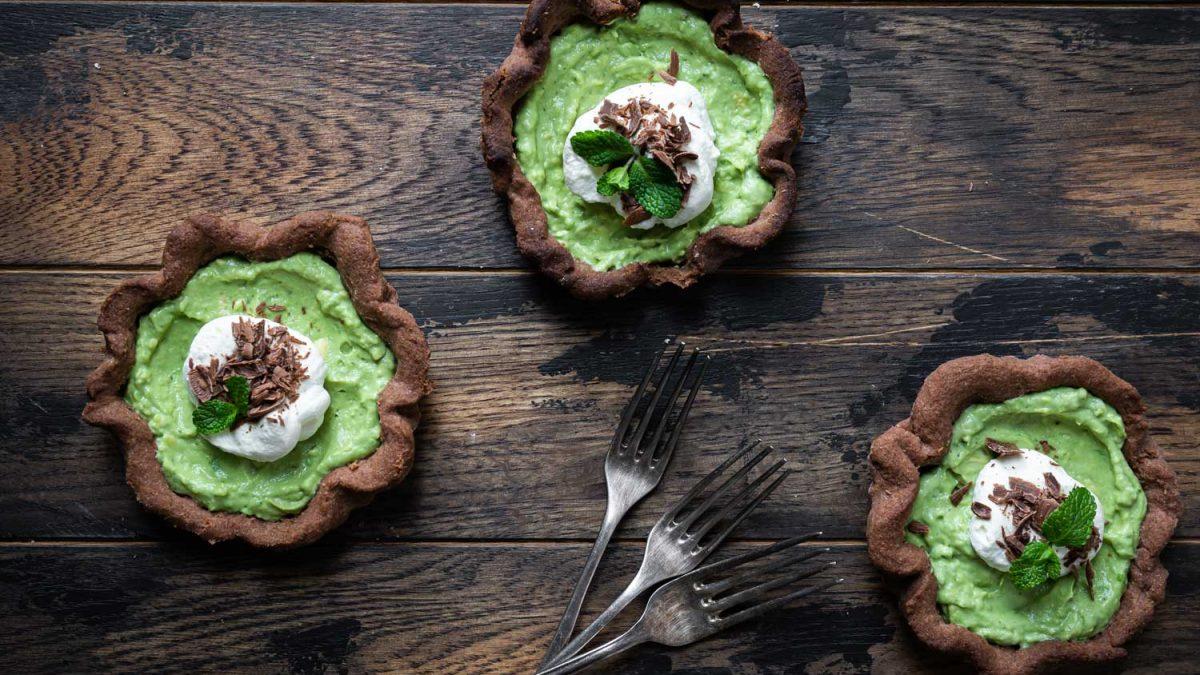 Avocado-Matcha-Törtchen angerichtet auf rustikaler Holzplatte