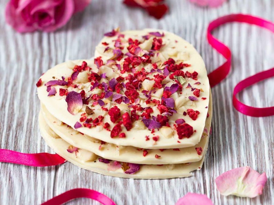 Weiße Schokoladeherzen mit gehackten Macadamia-Nüssen für Valentinstag
