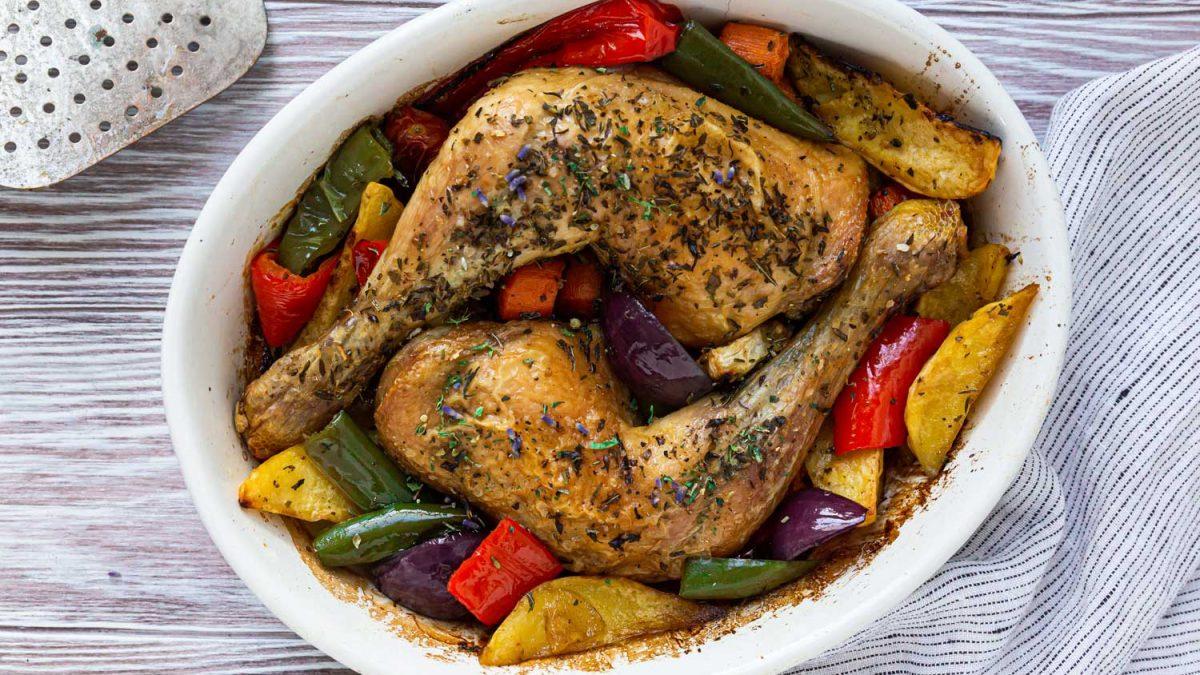 Hühnerkeulen aus dem Ofen in Ofenform auf Gemüse angerichtet
