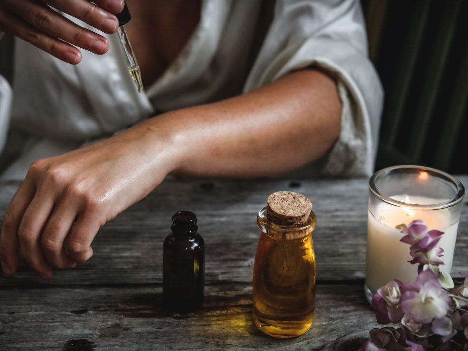 Eine Frau tropft in einem stimmigen Setting, neben einer brennenden Kerze Massage-Öl auf ihren Unterarm