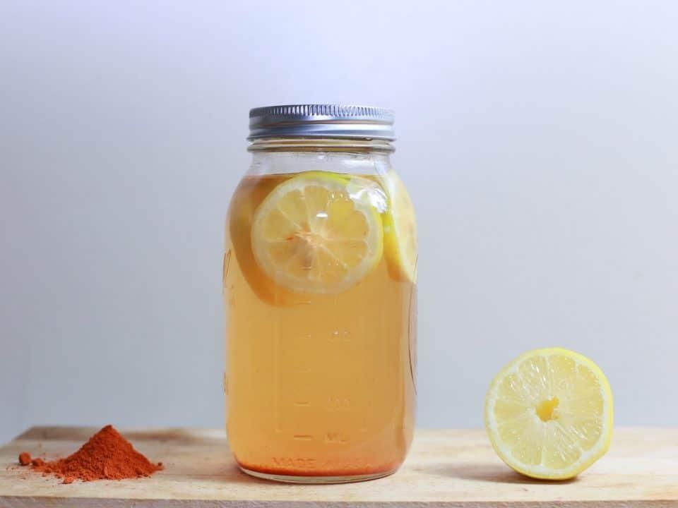 Kurkumapulver, ein Einmachglas mit Kurkuma-Shots und eine halbe Zitrone liegen auf einem Holzbrett vor hellgrauem Hintergrund