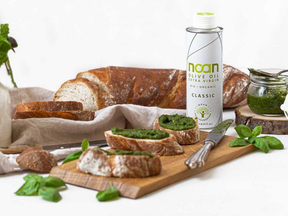 NOAN Kräuterpesto auf Brot, angerichtet mit Basilikum-Blättchen und NOAN Classic auf einem Holzbrett