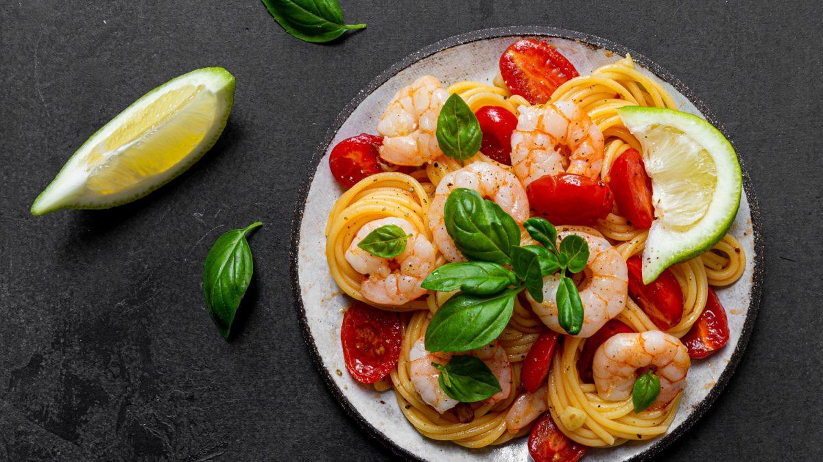 Pasta mit Garnelen, angirchtet mit Kirschtomaten und frischem Basilikum