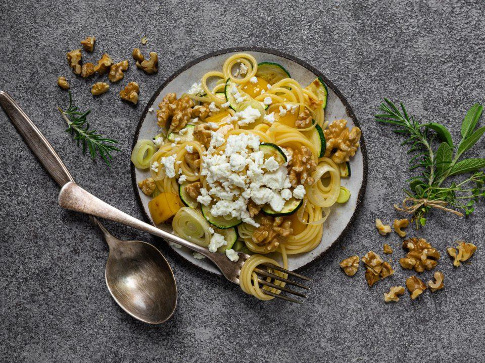 Spaghetti mit Walnüssen, Feta und NOAN Herbs angerichtet auf einem Teller mit Besteck und Kräutern