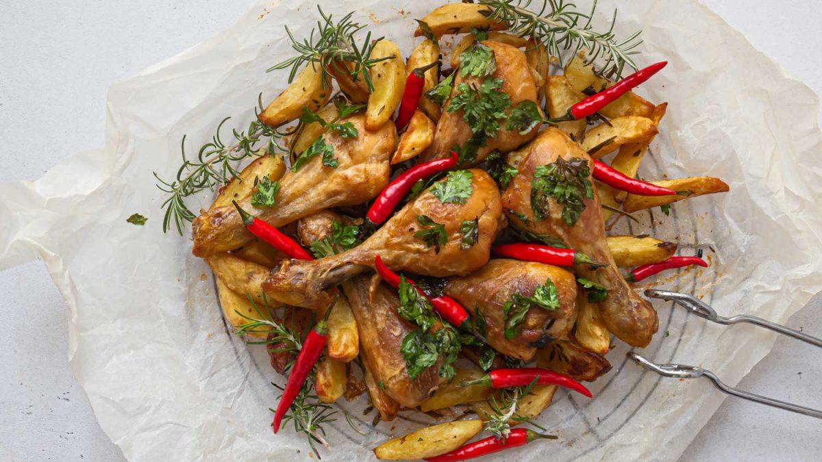 Hühnerkeulen und Kartoffelspalen angerichtet auf einer Platte mit roten Chilis, Rosmarin und Petersilie
